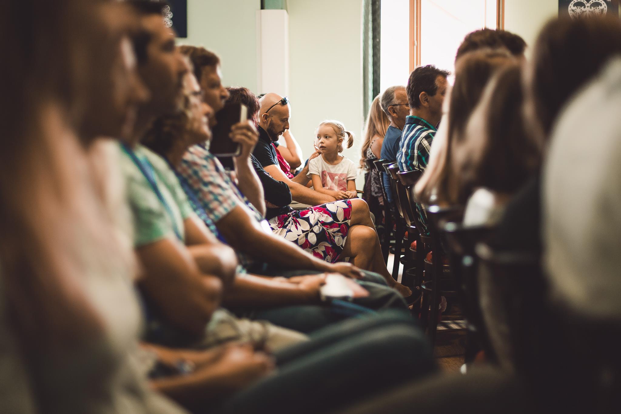 účastníci sledují řečníka na bohoslužbě