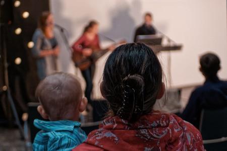 diváci sledující kapelu na bohoslužbě